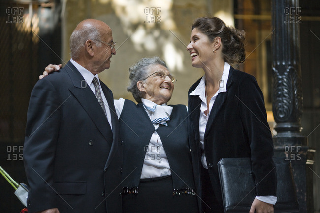 Businesswoman and businessman smiling and talking with a senior woman.