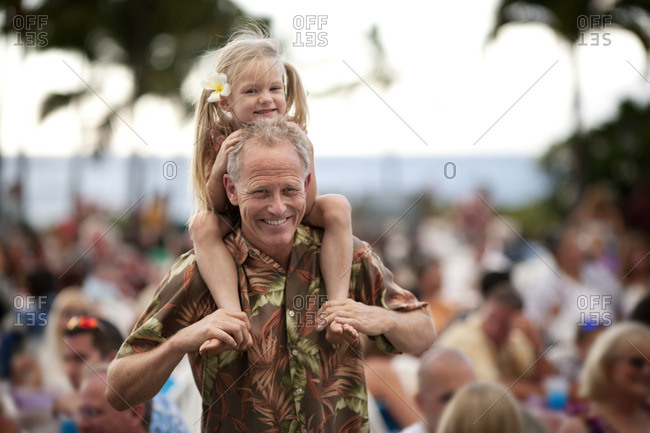 Man carrying his granddaughter on his shoulders.