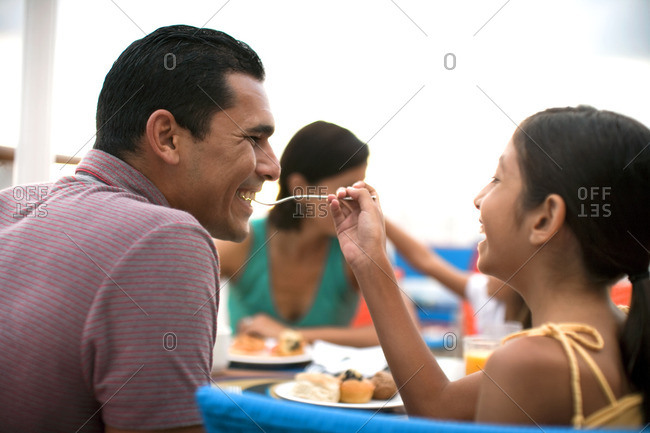 Young girl giving her father a taste of her food during an outdoor meal.