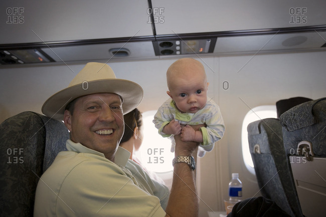 Man holding up his baby during an airplane journey.