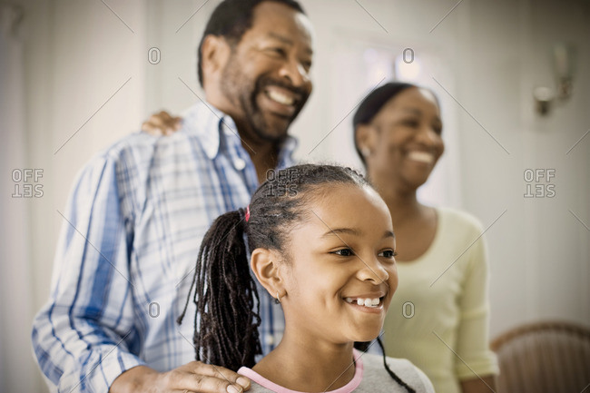 Smiling mother and father with their young daughter.