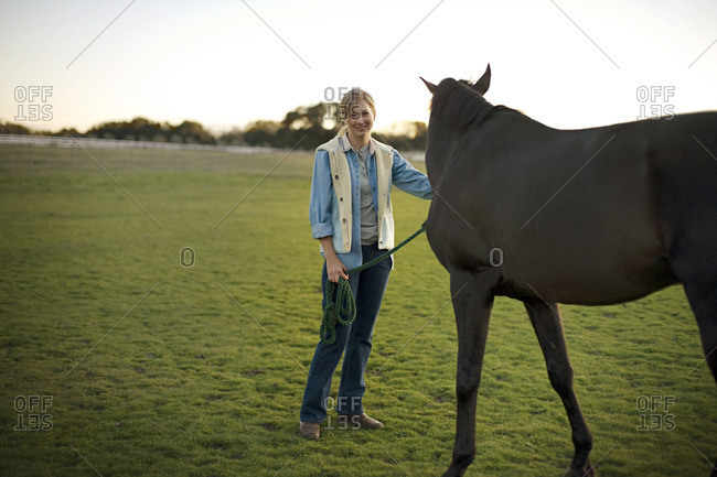 Woman with her horse in a field.