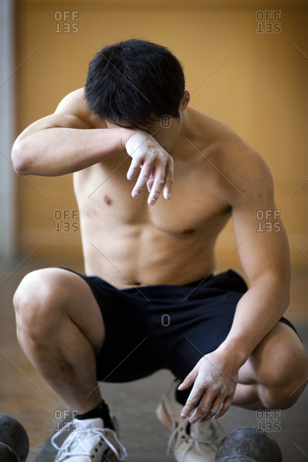 Athlete wiping his brow during a workout session.