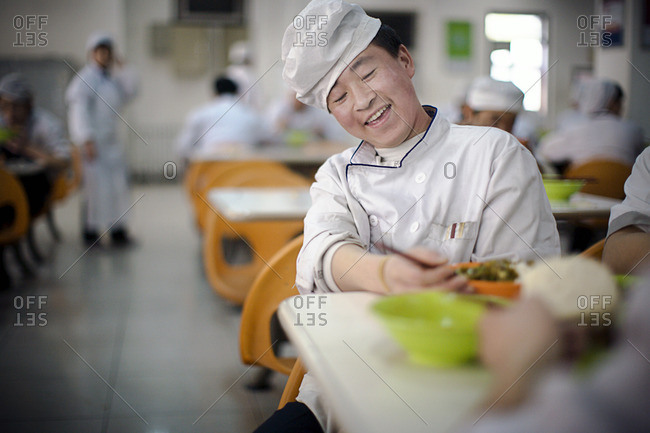 Chef preparing food in a large cafeteria.