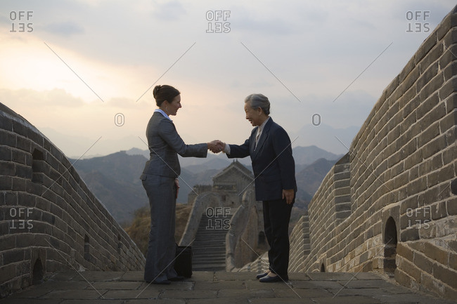 Two businesswoman shaking hands on the Great Wall of China.