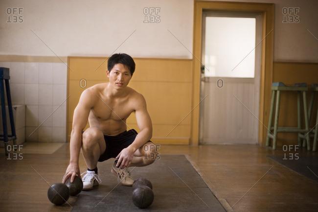 Athlete using medicine balls in a gym.