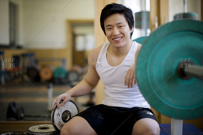 Young man working out with weights in a gym.