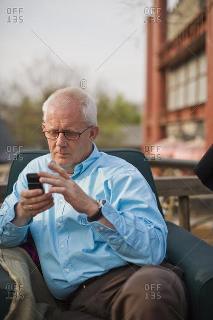 Senior man using his cellphone on a balcony.