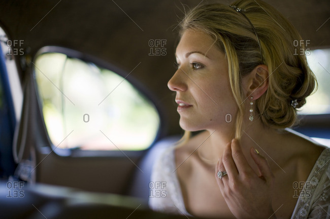 Bride in the backseat of her wedding car.