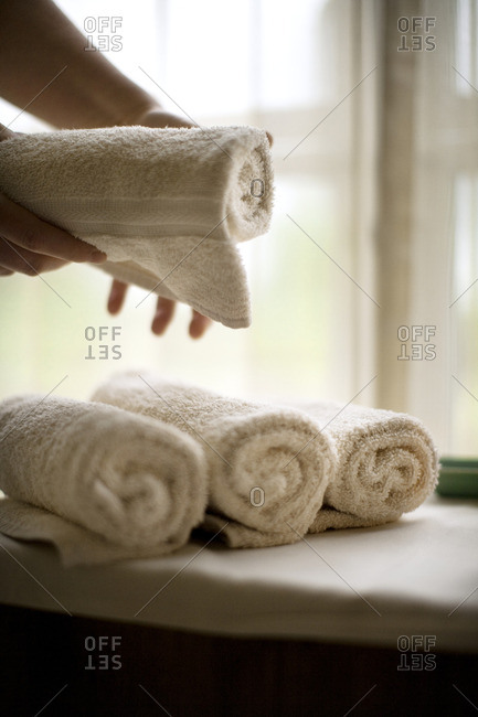 Maid placing rolled up towels in a hotel.