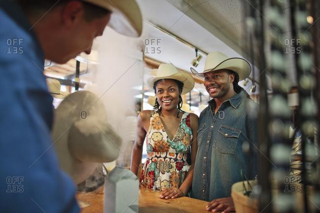 Couple wearing cowboy hats at a souvenir store.