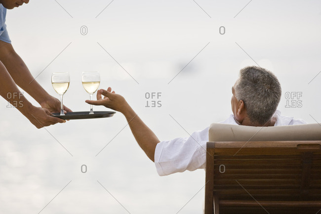 Man relaxing on a sun lounger being served a glass of wine.