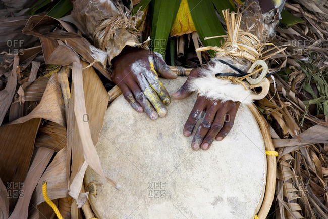 Traditional musician playing a drum.