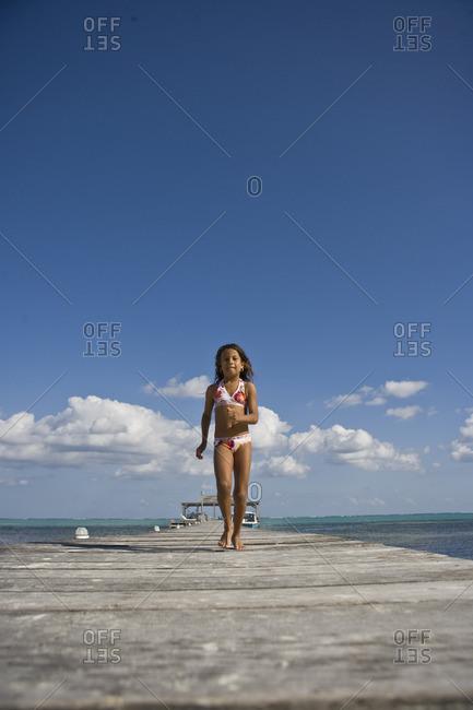 Young girl running along a pier.
