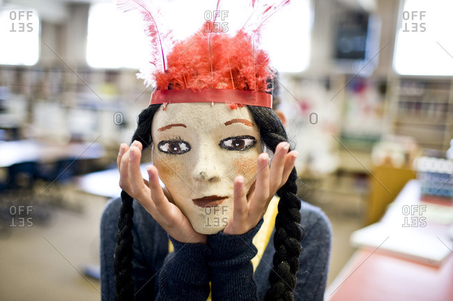 Person wearing a paper mache mask.