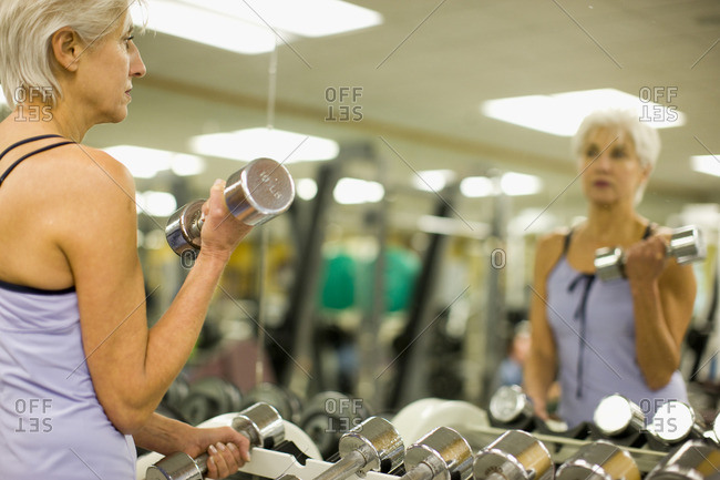 Woman working out with dumbbells in a gym.