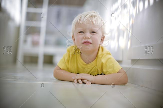 Grumpy toddler boy lying on the floor.