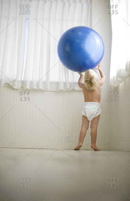 Toddler boy playing with an exercise ball.
