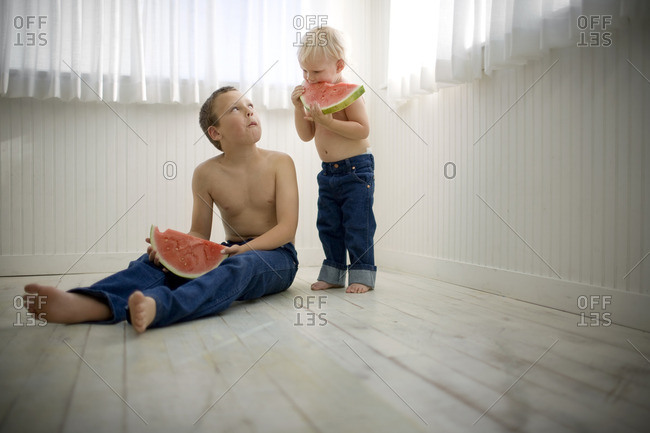 Two young brothers eating watermelon slices.