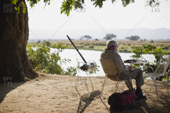 Senior man fishing and writing by a rural river.