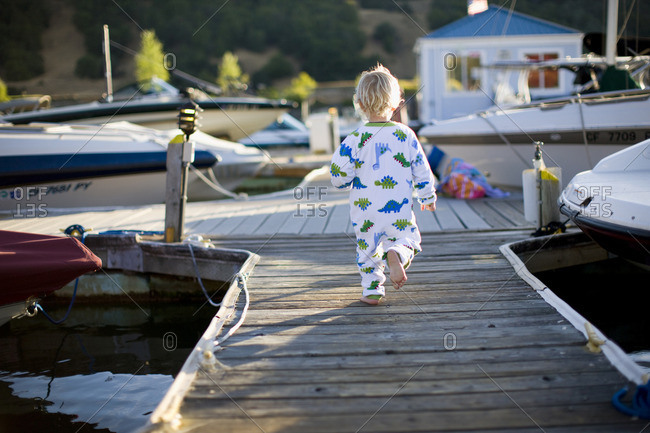 December 15, 2016: Toddler boy in his pajamas running along a pier.