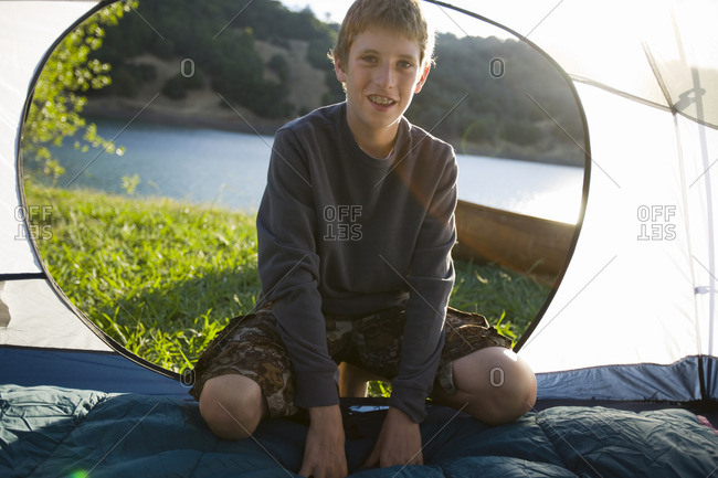 Young boy in his tent while camping by a lake.