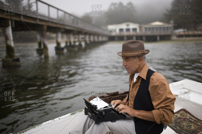 Writer using a typewriter on a small boat.