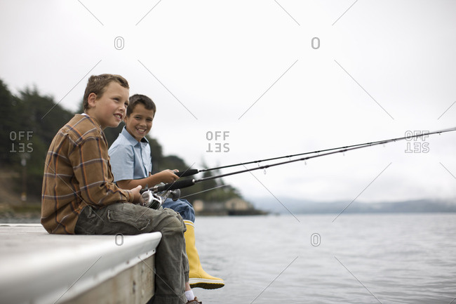 Two young boys fishing at the edge of a pier.