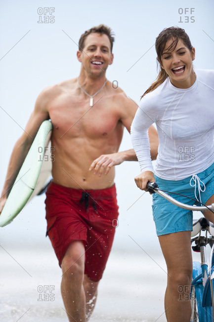 Couple running along the beach with a surfboard and bike.