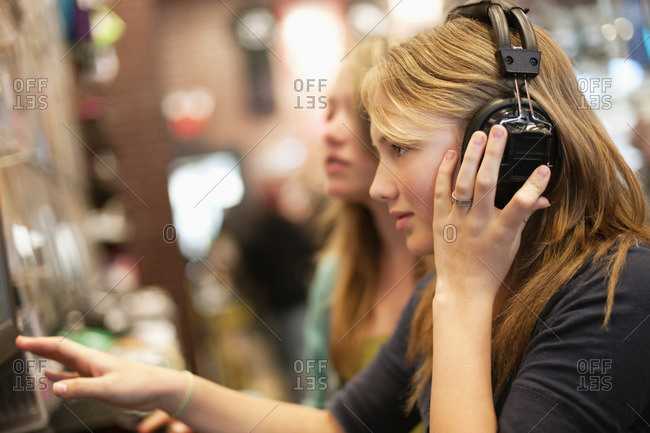 Teenage girls listening to music in a music shop.