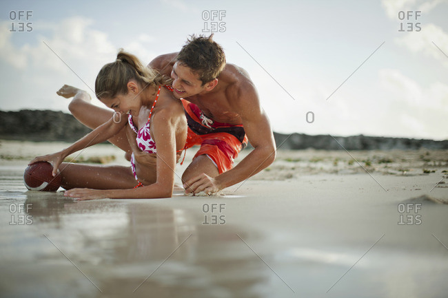 Young couple playing football on the beach.