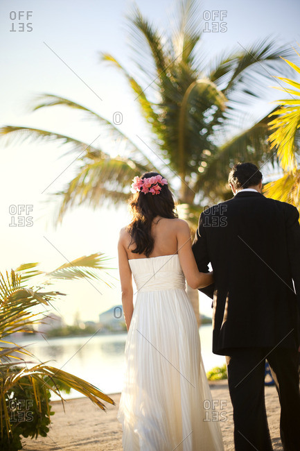 Bride and groom walking arm in arm on the beach.