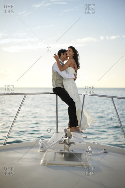 Bride and groom embracing on the bow of a boat.