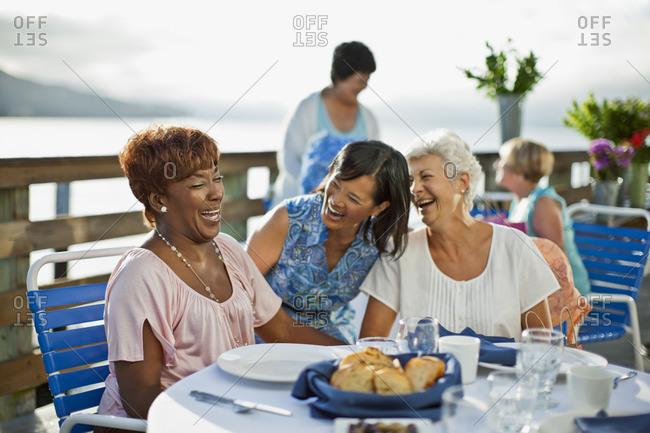 Friends enjoying a meal on a waterside restaurant.