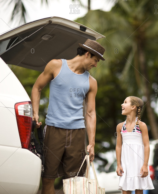 Father and daughter unloading the car, after arriving at their vacation destination.