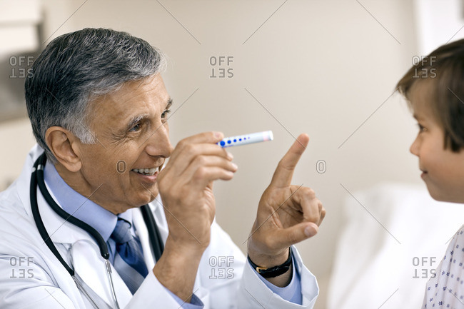 Doctor examining a young patient's eyes.