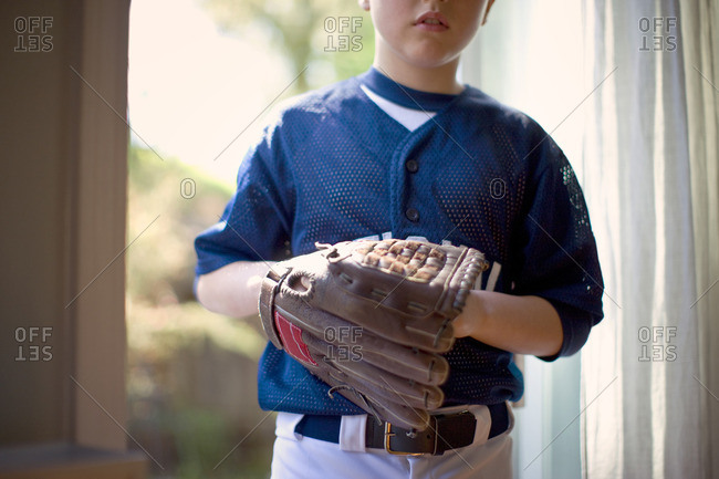 Young boy wearing a baseball glove.