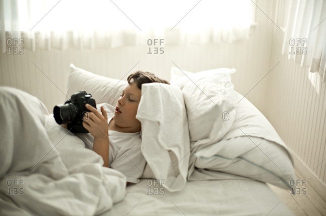 Young boy looking at a camera while lying in bed.