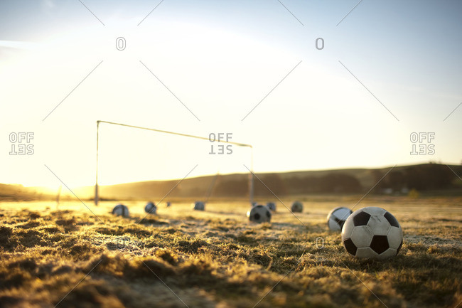 Soccer balls on a field at sunset.