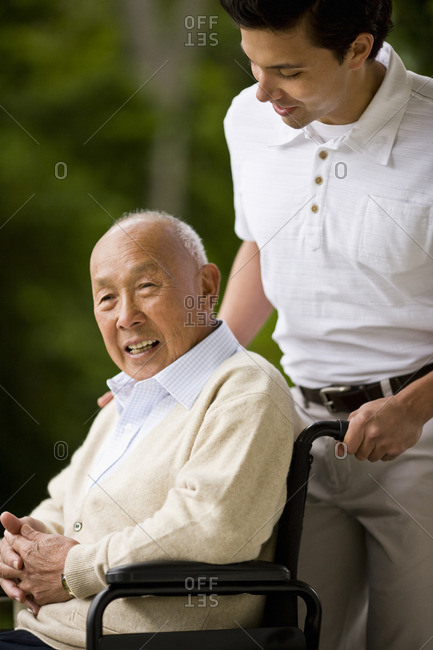Young man pushing a senior man in a wheelchair.