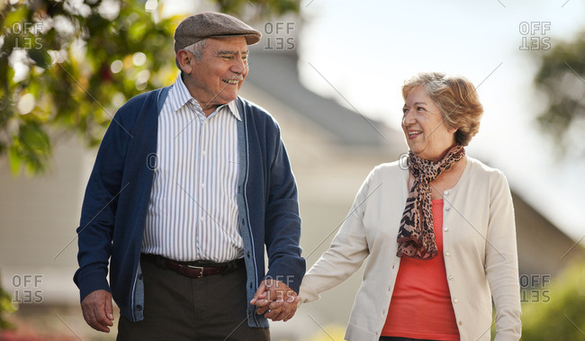 Senior couple holding hands while walking together.