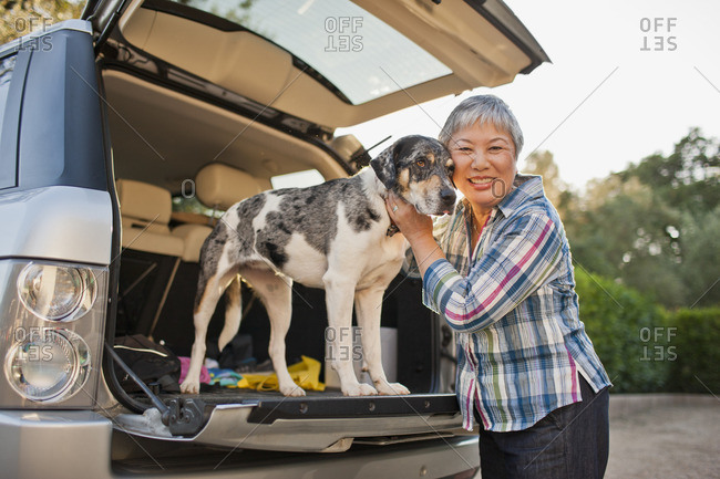 Senior woman with her dog on a road trip.