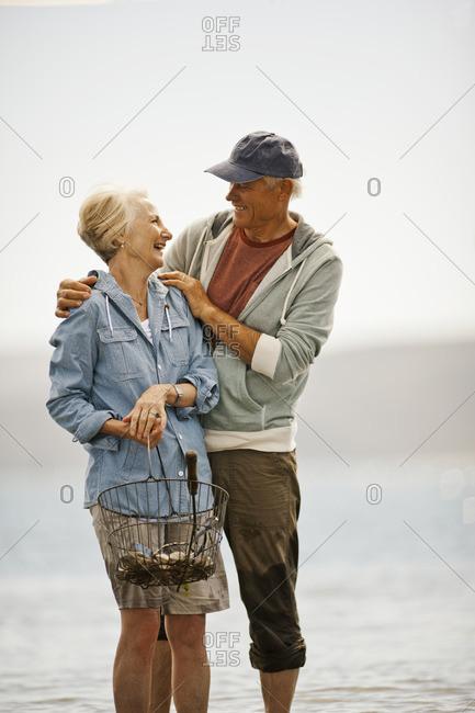 Senior couple gathering shellfish at the beach.