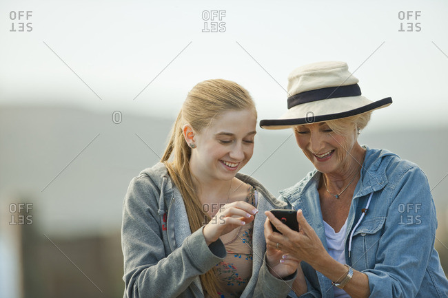 Teenage girl and her grandmother looking at a cellphone.