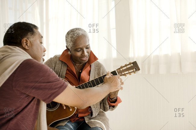 Man teaching his partner to play the guitar.