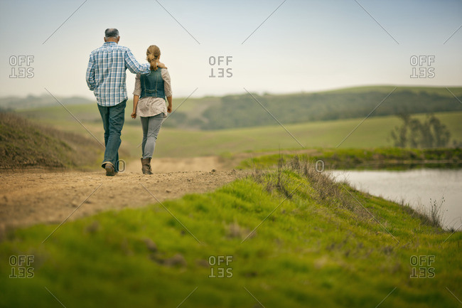 Couple walking along a footpath next to a river.