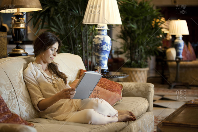 Young woman reading a book on the couch.