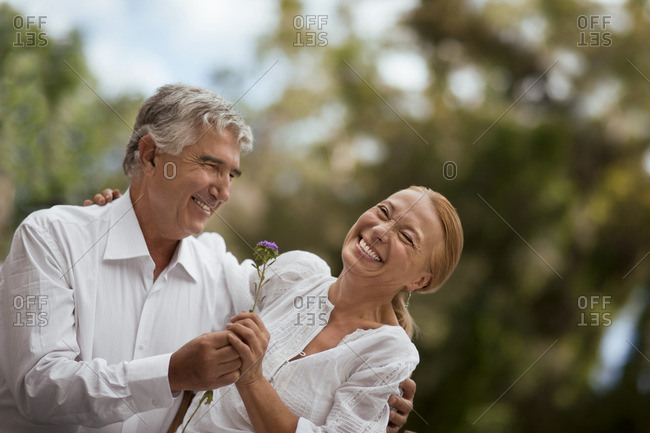 Man giving a flower to his partner.