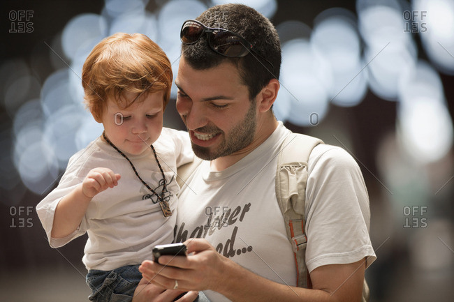 Father showing his toddler son something on a cellphone.