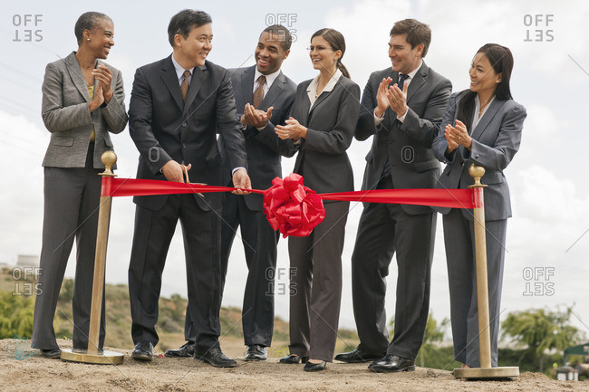 Businesspeople cutting a ribbon for a new business.
